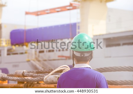 Photo of backs of workers interacting and looking at cargo ship