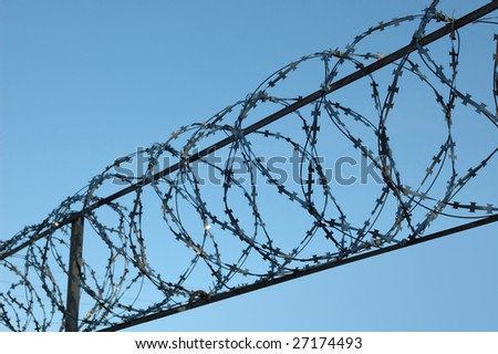 Photo of barbed wire and blue sky - stock photo