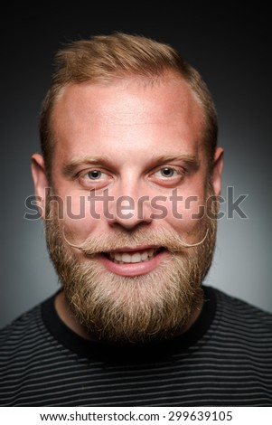 Photo of bearded man showing his teeth on black. Happy man satisfying his photosession in studio.
