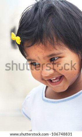 Photo of beautiful and blissful indian baby girl with expressive eyes and photogenic face expressing toddler's innocence with a pretty smile. The child is of pre school age and is of indian origin. - stock photo