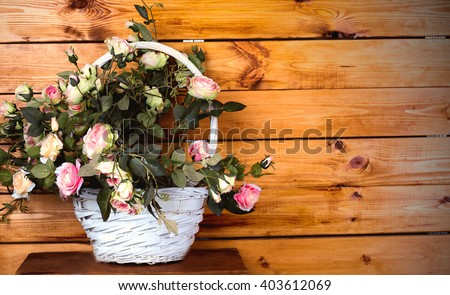 photo of Beautiful artificial roses in a wicker basket