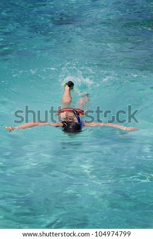 Photo of beautiful asian girl snorkeling in crystal clear Maldive waters with ripples. - stock photo