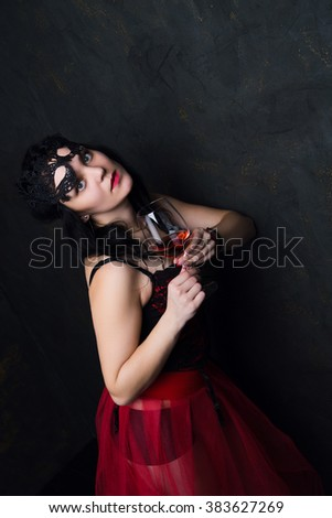 photo of beautiful brunette woman holding a glass of red wine - stock photo