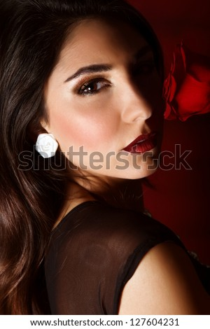 Photo of beautiful brunette woman with red rose isolated on dark background, closeup portrait of gorgeous female with perfect makeup, luxury beauty salon, Valentine day, passion and elegance concept - stock photo