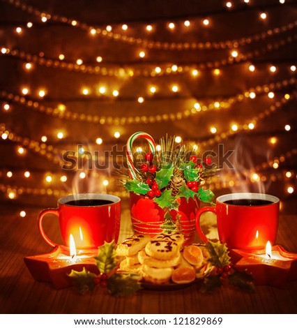 Photo of beautiful Christmas still life, red tea cups with tasty homemade cookies and candles on the wooden table on shiny brown background, electrical garland glowing on the wall, candy cane - stock photo