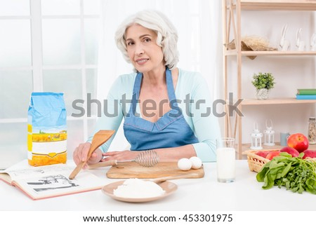 Photo of beautiful emotional adult woman. Nice kitchen with window. Woman reading recipe