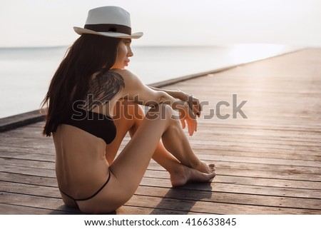 Photo of beautiful fit lady in white hat and black bikini laying on the pier on picturesque seascape background,looking at sunset sky,wing,toned body,full lips,beach at sunset, retro style color tones