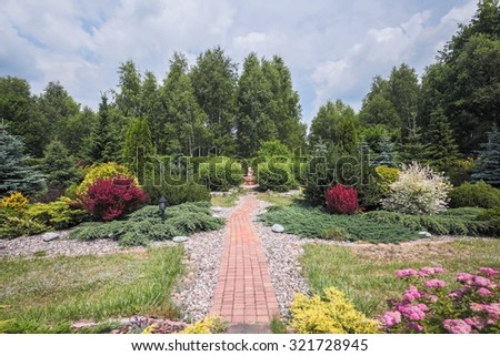 Photo of beautiful garden with blooming bushes and cobbled path - stock photo