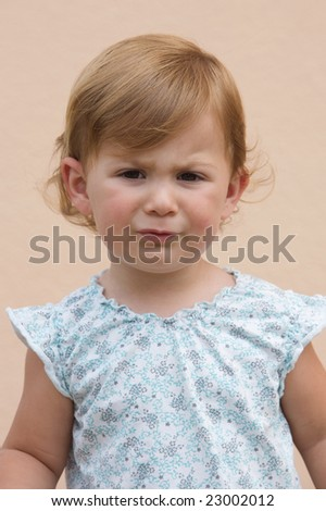 Photo of beautiful girl frowning with funny expression - stock photo