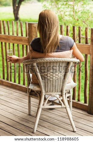 Photo of beautiful girl sitting on veranda and enjoying calm weather, rear view of blond female sit in chair on the balcony, drinking healthy mineral water and watching for peaceful nature - stock photo