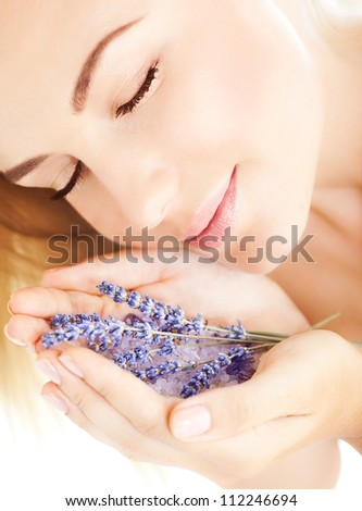 Photo of beautiful girl smell purple lavender flowers, closeup portrait of cute woman with closed eyes and holding sea salt and violet flower in hands, pretty female with clean skin, spa concept