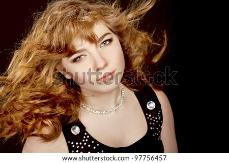 Photo of beautiful girl with magnificent red hair isolated on black salon - stock photo