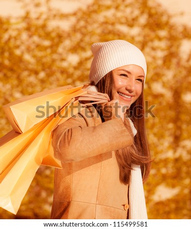 Photo of beautiful girl with shopping bag, closeup portrait of attractive female isolated on autumn foliage background, young lady enjoying her purchase, autumnal sales, spending money - stock photo