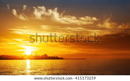 Photo of beautiful orange sunset on the sea, silhouette of lebanese city in sunrise on seashore, peaceful landscape, sun down on town on coast, warm weather, romantic vacation, holiday concept - stock photo