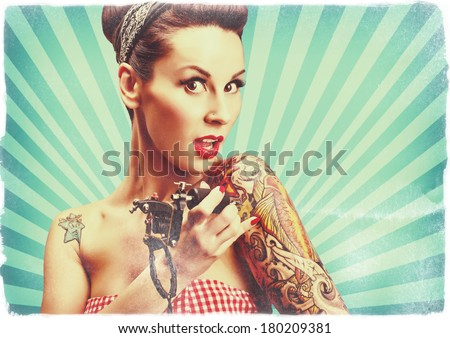 Photo of beautiful pin-up girl with tattoos and tattoo machine tattooing herself and looking at the camera. Retro styled imagery, toned image, grungy, noise added. - stock photo