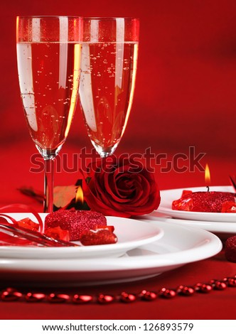 Photo of beautiful red romantic table setting, white festive utensil with romantic decorations, two glass of wine, alcohol beverage, rose flower, Valentine day, romance and love concept