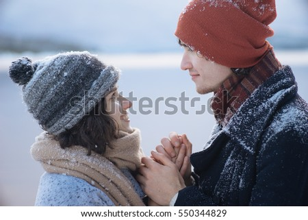 Photo of beautiful romantic couple looking at each other on winter nature