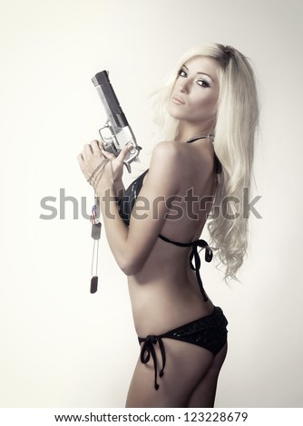 Photo of beautiful slim sexy blond young woman holding a pistol and dog tags in bikini. - stock photo