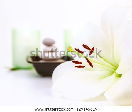Photo of beautiful white lily flower, pebble stones, two candles, spa still life, dayspa, luxury beauty salon, hygiene items, bath objects, healthy lifestyle, organic cosmetics, resort concept - stock photo