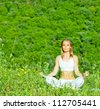 Photo of beautiful woman doing yoga exercise outdoors, mental health, healthy lifestyle, cute young lady sitting in lotus pose, pretty girl is engaged in fitness in park over green trees background - stock photo
