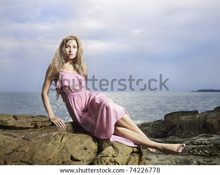 Photo of beautiful woman in wet clothes on a rocky seashore
