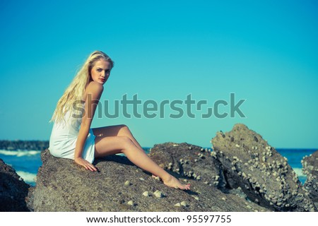 Photo of beautiful woman in wet clothes on a rocky seashore - stock photo