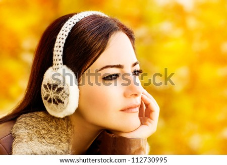 Photo of beautiful woman wearing clothing for head, closeup portrait of attractive arabic female on golden autumn background, pretty young brunette lady in warm earmuff, fall season concept - stock photo
