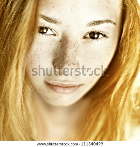 Photo of beautiful woman with freckled skin on her face - stock photo