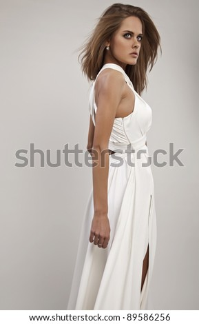 Photo of beautiful woman with magnificent hair which posing in luxury silk dress - stock photo