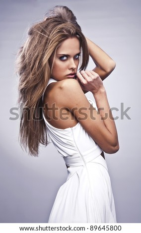 Photo of beautiful woman with magnificent hair which posing in luxury white silk dress. - stock photo