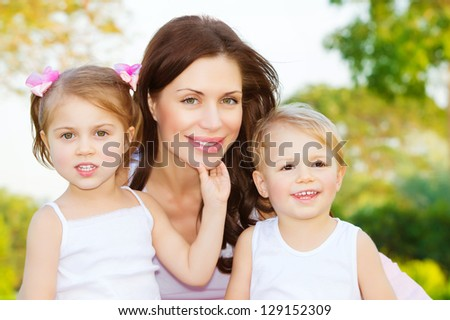 Photo of beautiful woman with two cute kids, closeup portrait of young mother with sweet daughter and lovely son outdoors, adorable children with mommy on the park in spring, happy family concept - stock photo