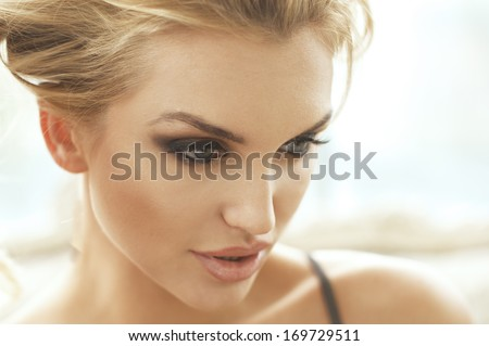 Photo of beautiful young blonde girl smiling, posing with her hands in hair.  - stock photo