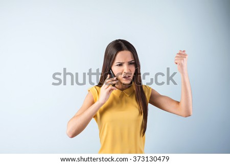Photo of beautiful young business woman standing near gray background. Angry woman with yellow shirt screaming while using mobile phone - stock photo
