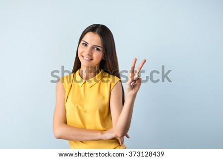 Photo of beautiful young business woman standing near gray background. Smiling woman with yellow shirt looking at camera and showing victory sign - stock photo
