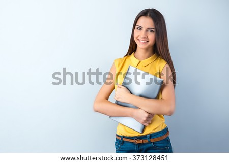 Photo of beautiful young business woman standing near gray background. Smiling woman with yellow shirt holding laptop and looking at camera - stock photo
