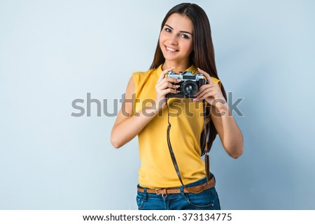 Photo of beautiful young business woman standing near gray background. Woman with vintage camera looking at camera and smiling - stock photo