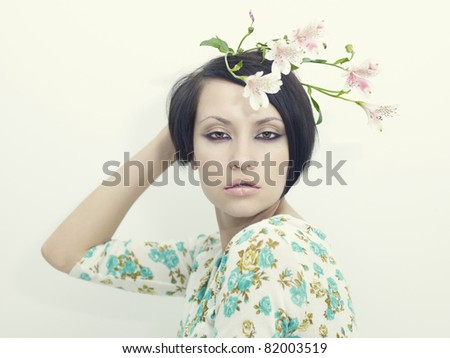 Photo of beautiful young girl with delicate flowers - stock photo