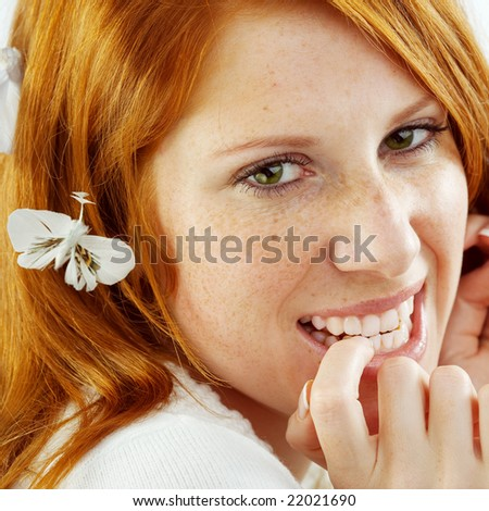 Photo of beautiful young girl with red hair and freckled skin on her face, square composition - stock photo