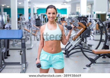 Photo of beautiful young sporty woman. Fitness girl training with dumbbells in sport club with exercise equipments. Woman smiling and looking at camera - stock photo