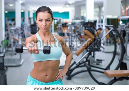 Photo of beautiful young sporty woman. Fitness girl training woth dumbbell in sport club with exercise equipments. Woman looking at camera. Focus on dumbbell - stock photo