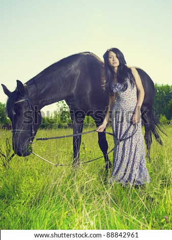 Photo of beautiful young woman and horse in summer field - stock photo