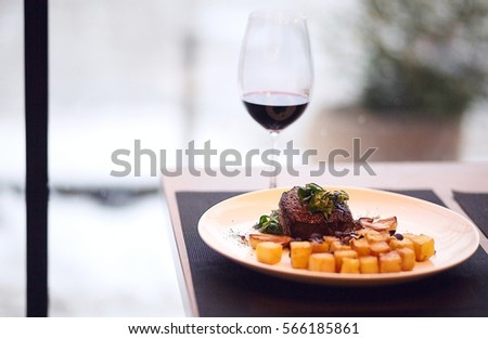photo of beef  Steak with roasted potato and glass of red wine