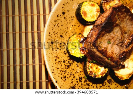 photo of beef steak with sauce, grill and fresh vegetables