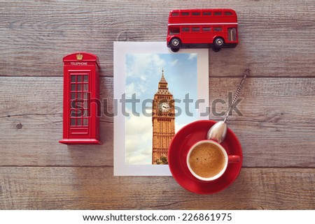 Photo of Big Ben in London on wooden table with coffee cup and souvenirs - stock photo