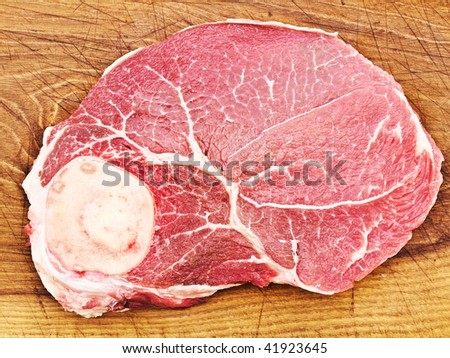 Photo of big piece of raw meat at wooden background