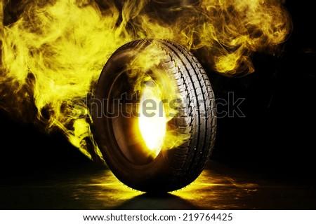 photo of black smoked and burning tire - stock photo
