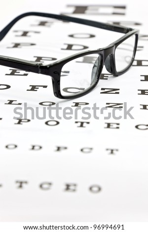 Photo of black spectacles on an eye test chart - stock photo
