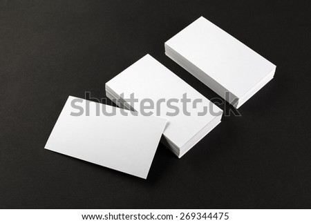 Photo of blank business cards on a black background. Template for branding identity. Top view. Shallow depth of field. - stock photo