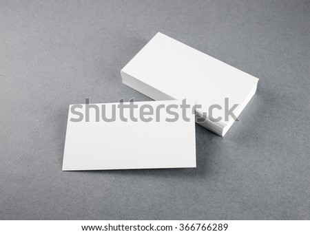 Photo of blank business cards with soft shadows on gray background. Mock-up for branding identity. Studio shot. - stock photo