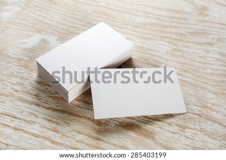 Photo of blank business cards with soft shadows on light wooden background. For design presentations and portfolios. - stock photo